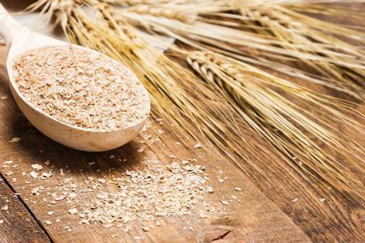 tarâțe de grâu in lingura de lemn cu spice de grâu alături
