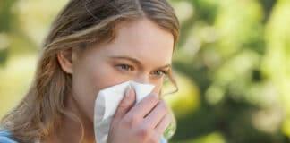 Rinita alergica femeie suflandu-si nasul in parc